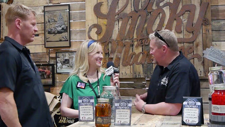 Michael Bender, Vice President of Sales, Ole Smoky Tennessee Moonshine & Shane McKnight, Director of Mixology, Best Beverage Catering chat Moonshine 101 with YBLTV Anchor, Erika Blackwell at Nightclub & Bar Show 2014 (Image Courtesy: Ole Smoky Tennessee Moonshine/Your Biz LIVE).