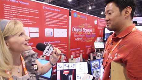 SoundGraph, Inc.'s Senior Project Manager, Kevin Lee demos their products to YBLTV Anchor, Erika Blackwell at Digital Signage Expo 2014. (Image Courtesy: SoundGraph, Inc./Your Biz LIVE).