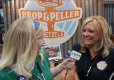 Claudia M. Hillmeier, President, BC International Trading & Business Support, Inc. talks Prop & Peller Pretzels with YBLTV Anchor, Erika Blackwell at Nightclub & Bar Show, 2014. (Image Courtesy: Prop & Peller Pretzels/Your Biz LIVE).